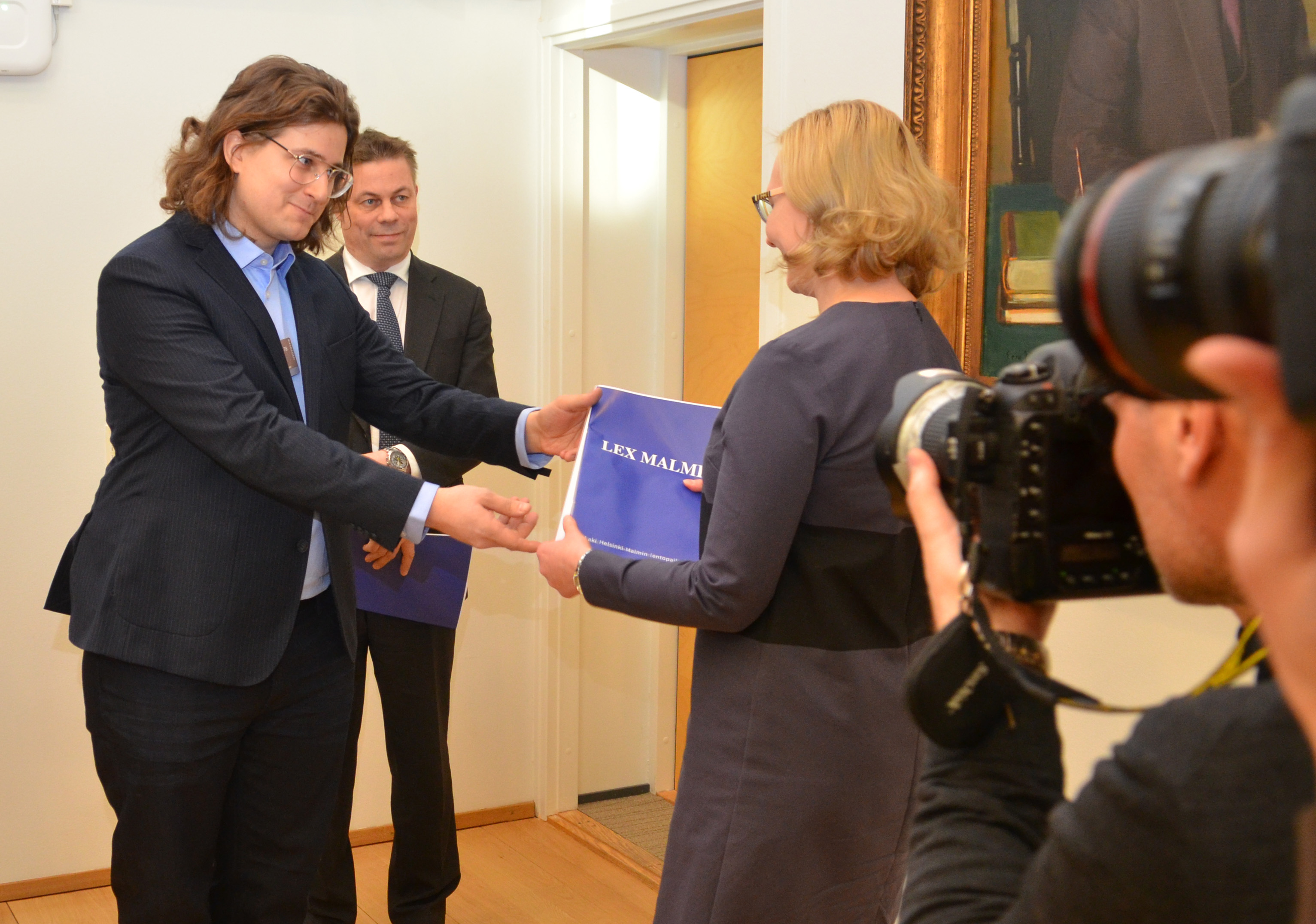 The initiator of Lex Malmi, Mr. Kim Korkkula presents the citizens' law initiative to the Speaker of Parliament Marja Lohela. Behind him is Chairman of Friends of Malmi Airport, Mr. Timo Hyvönen. Photo: Raine Haikarainen / Friends of Malmi Airport